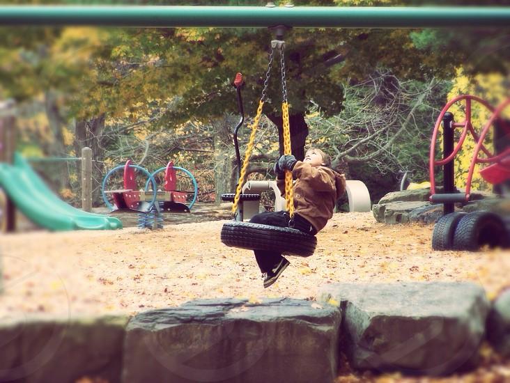 Child sitting on tire in playground photo