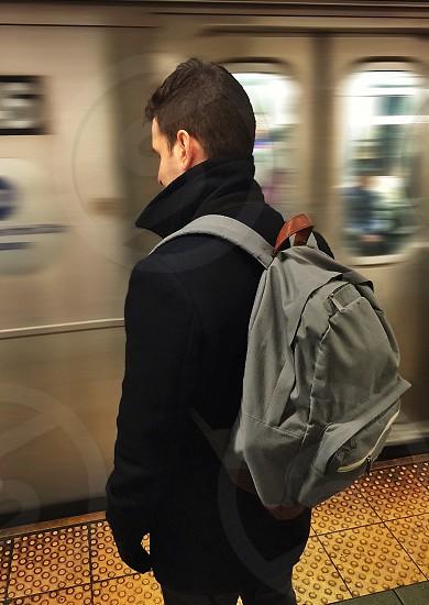 timelapse photogprahy of man standing near gray train photo