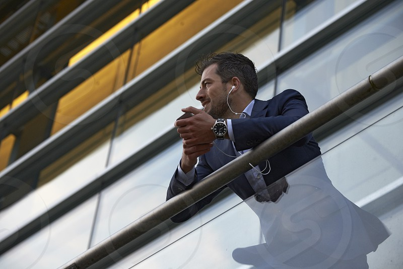 Successful businessman standing on a balcony outside office tower looking out into the world photo