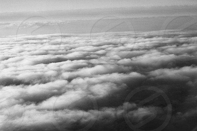 A black and white shot of clouds at elevation from an airplane photo