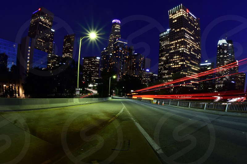 time lapse photography of empty gray paved road through high rise buildings photo