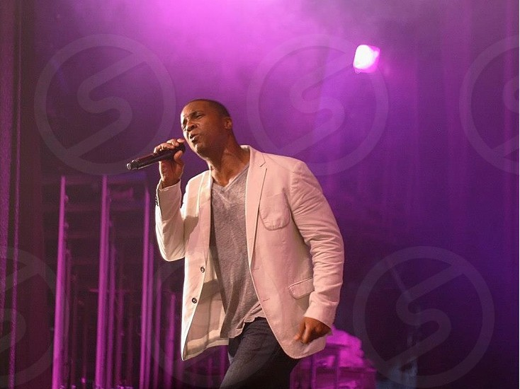 man singing on stage photo