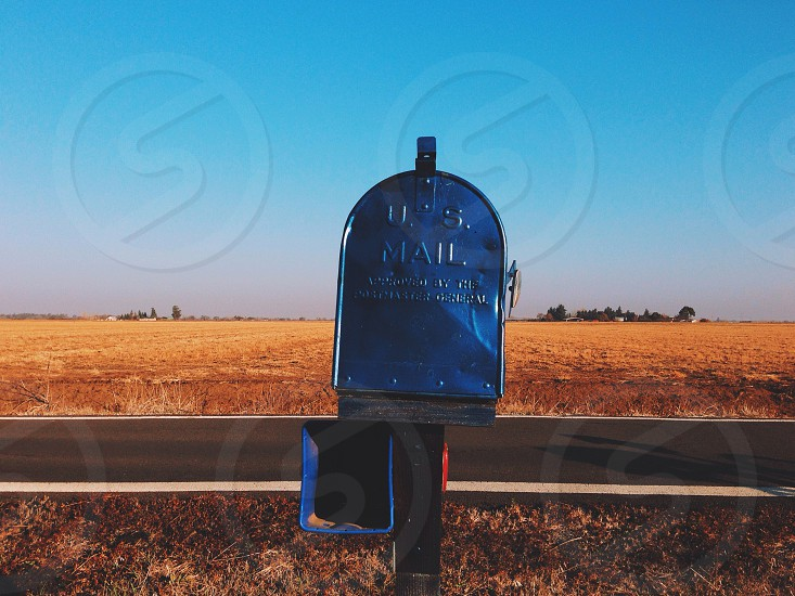 us mail box on top of wooden fence photo