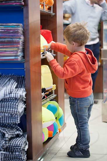 Cute little boy shopping for a beach accessories standing at a display rack at a store searching through colorful merchandise photo