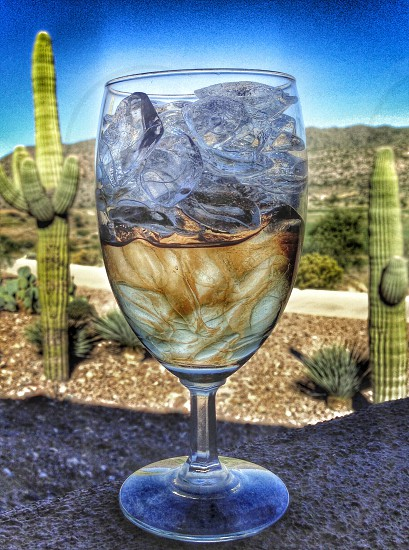 clear short stemmed glass with ice cubes photo