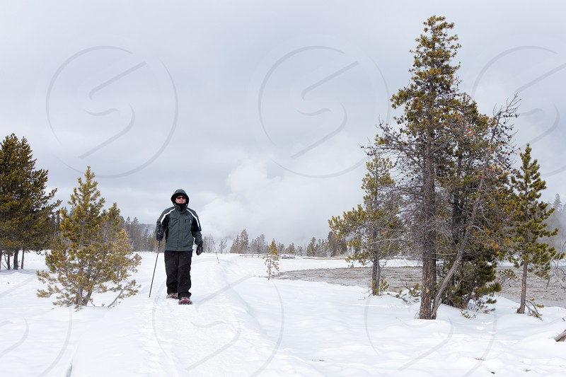 A man snowshoeing through the geyser area of Yellowstone National Park.  As seen on a tour from West Yellowstone Montana.  Release available upon request. photo