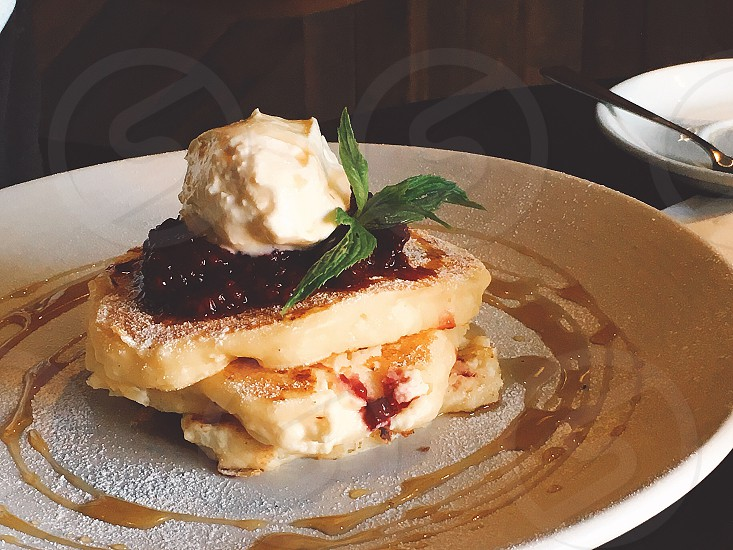 Fluffy pancakes with fruit preserves and clotted cream for breakfast photo