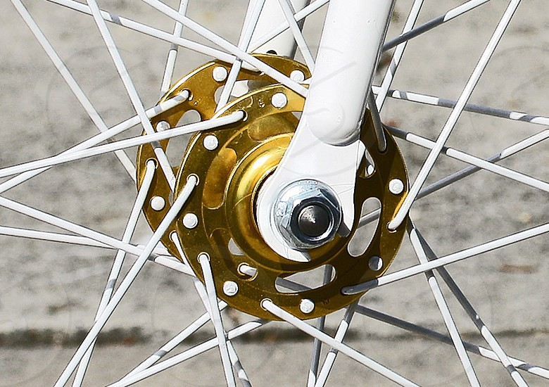 Close-up of a gold hub and white spokes of a bicycle. photo