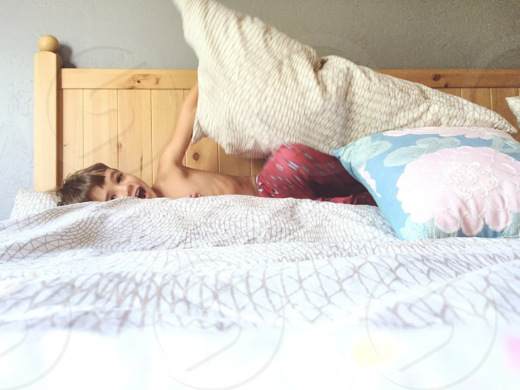 topless boy in red pajama pants holding white pillow while lying on white bed photo