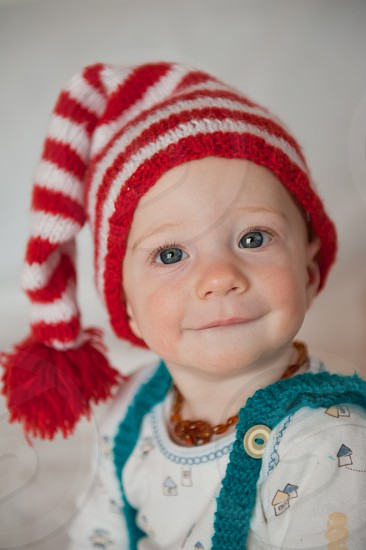 baby in white crew neck shirt wearing red and white stripe knit cap photo