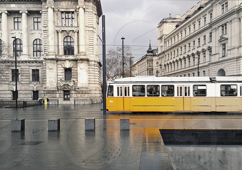 yellow and white tram on road near concrete building under cloudy sky during daytime photo