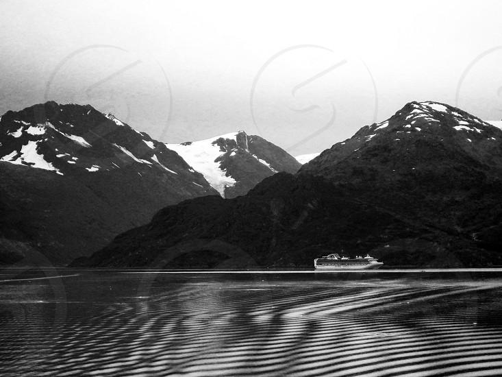 view of the white cruise ship near green mountain photo