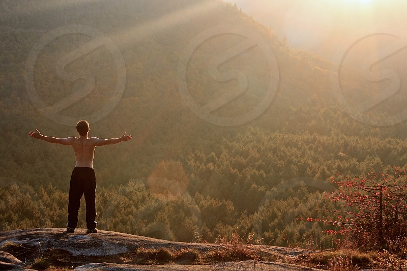 topless man standing on rock facing mountains photo