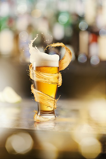 A cold glass of beer with beer foam and splash around on a wooden bar counter and blurred background with many bokeh photo