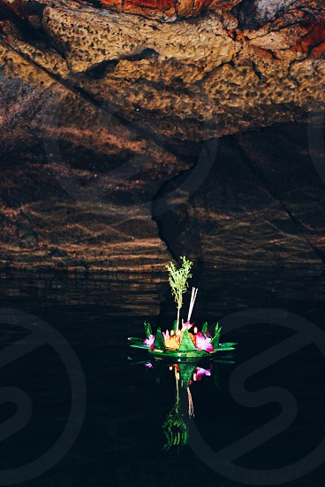 "Releasing a ""Kratong"" offering which are released into the cave after sunset and light up the cave at night photo"