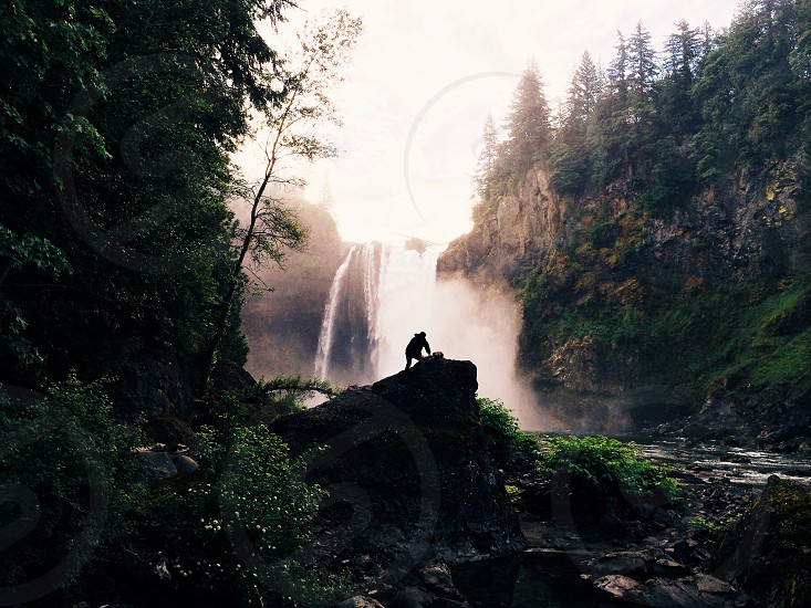 view of man at the forest with waterfalls photo