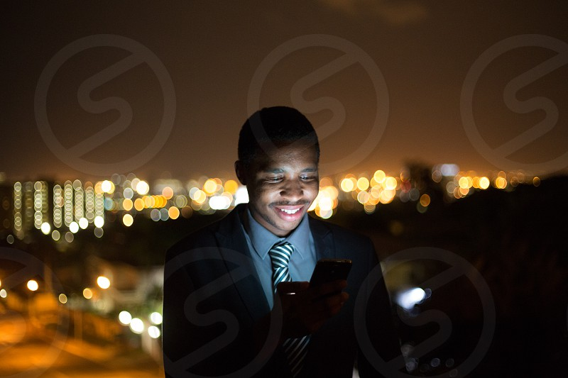 man in black suit blazer wearing white and blue stripe necktie smiling carrying black android smartphone  during night photo