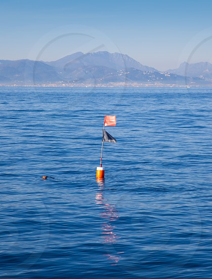 Longliner and trammel net buoy with flag pole in blue sea photo
