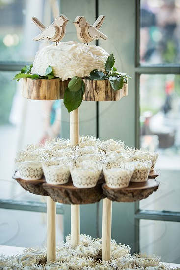 A cupcake display topped with a small cake with two birds at a wedding reception photo