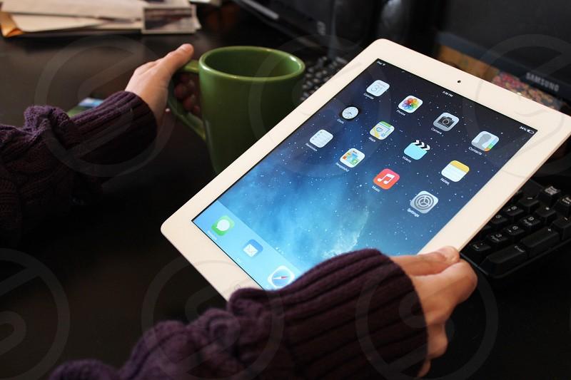person holding white apple ipad photo