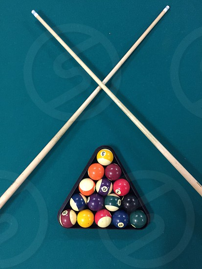 billiards balls and 2 brown pool sticks on green surface photo