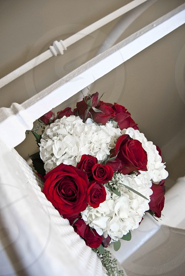 Red & white bridal bouquet on a spiral staircase. photo