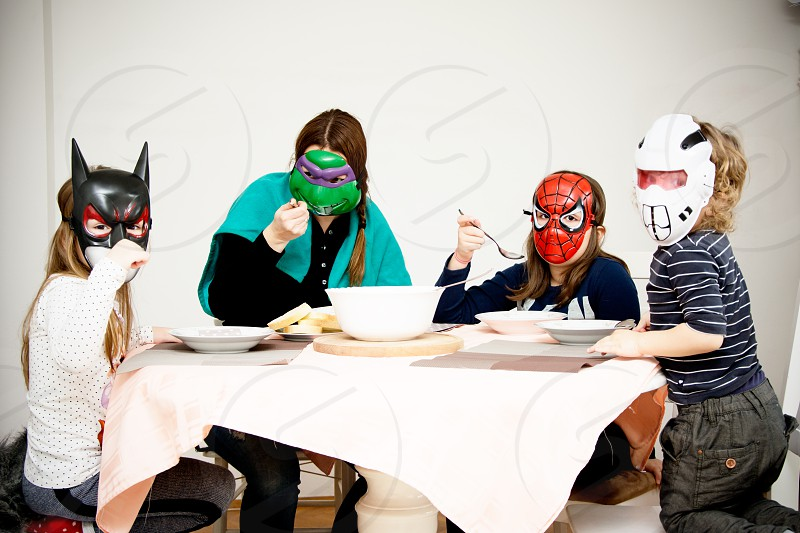 Dinner with super hero masks on...mother and three kids playing super heroes at the dinner table photo