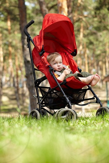 Outdoor portrait of the little boy sitting in the red buggy eating doughnut-shaped bread roll and looking to the camera. Natural light real colors shallow DOF (prime 35mm L lense). photo
