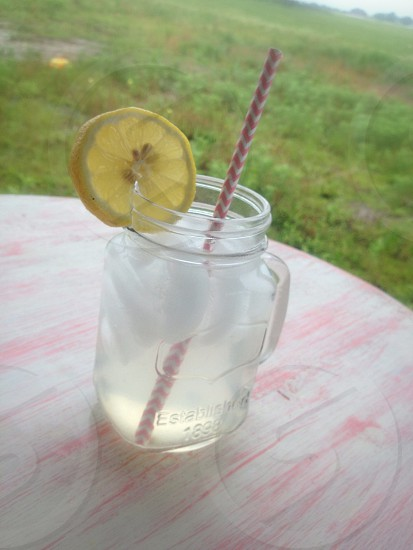 clear glass jar with lemon wedge on mouth photo