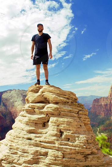 Rocks hiking angles high above adventure adrenaline standing elevation mountains wild hiking flying floating happy smiles smiling black clothing sky air Zion photo