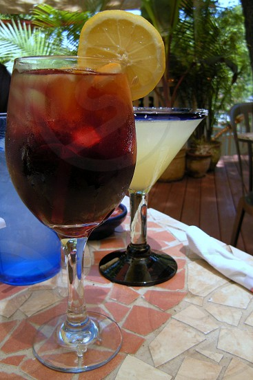 Sangria in wine glass with orange slice and lime margarita in oversized glass on mosaic table with ferns photo