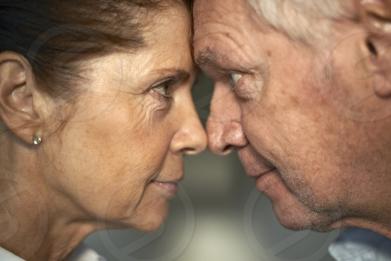Side profile of an elderly couple with their foreheads touching looking each other in the eyes photo