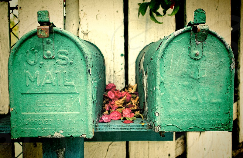 A pair of retro mailboxes near a white fence. photo