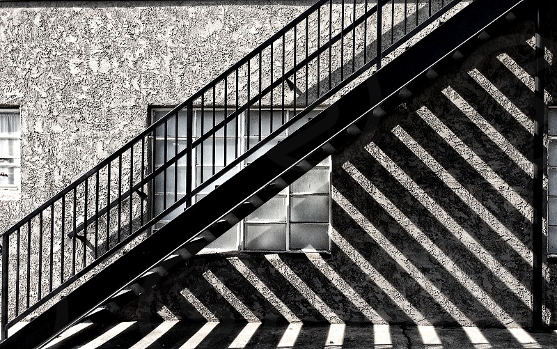 Sunlight streams through an outdoor staircase creating a pattern of angled shadows on the wall. photo