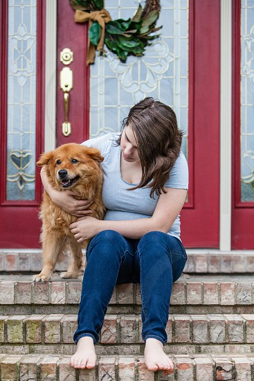 Girl sitting on the front porch with a dog. photo