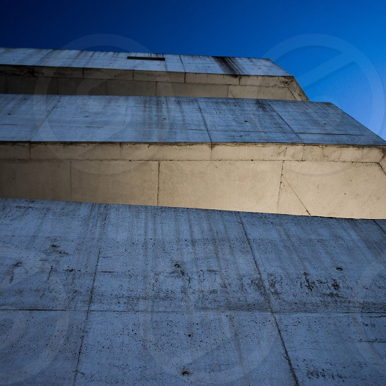 grey concrete building under blue sky in low-angle photography photo
