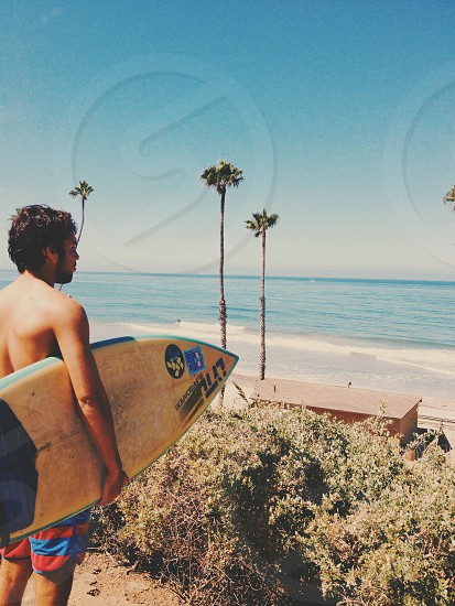 man holding white surfboard by the beach photo