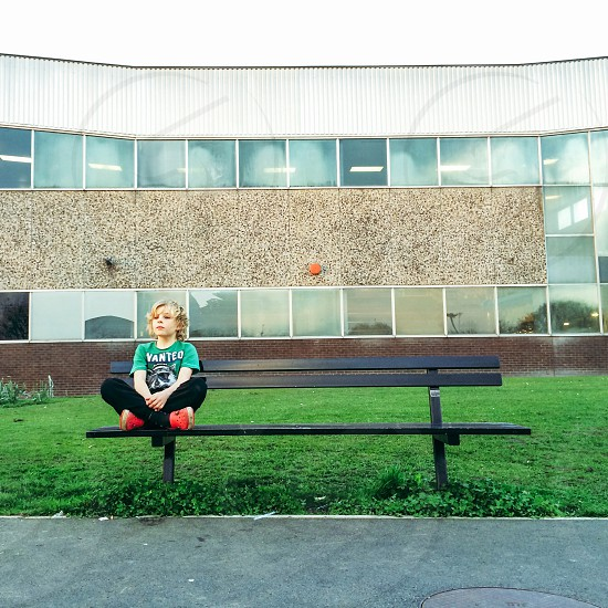 child in teal graphic crewneck t-shirt sitting on black bench chair photo