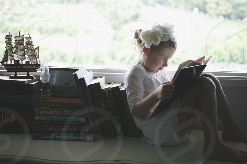girl reading on a window sill leaning on books photo