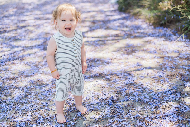 baby girl wearing white and black stripes sleeveless onesie standing on concrete platform surrounded by white and purple flowers photo