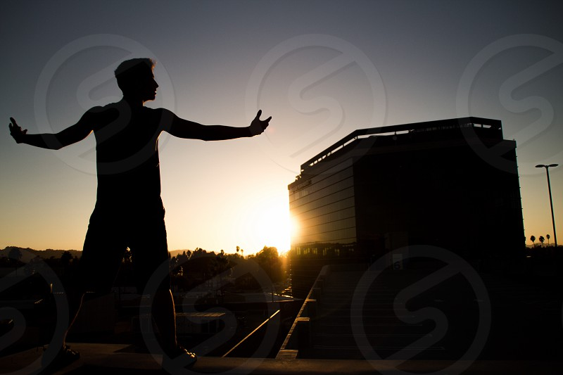 man's silhouette with stretching arms photo