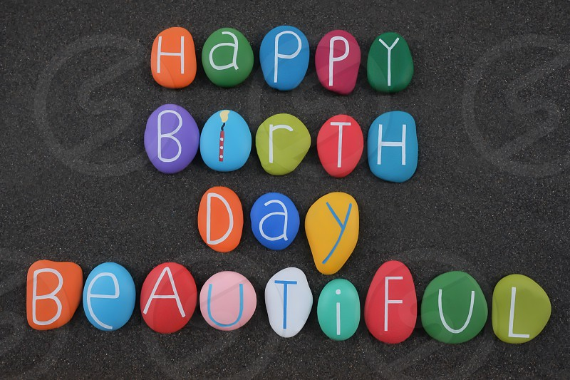 Happy Birthday Beautiful creative composition text with multi colored stone letters over black volcanic sand photo