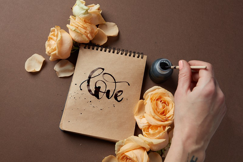 Female's hand using ink for writing word love in diary or notebook in Valentine's Day. Notebook with brown pages represented with orange flowers. photo