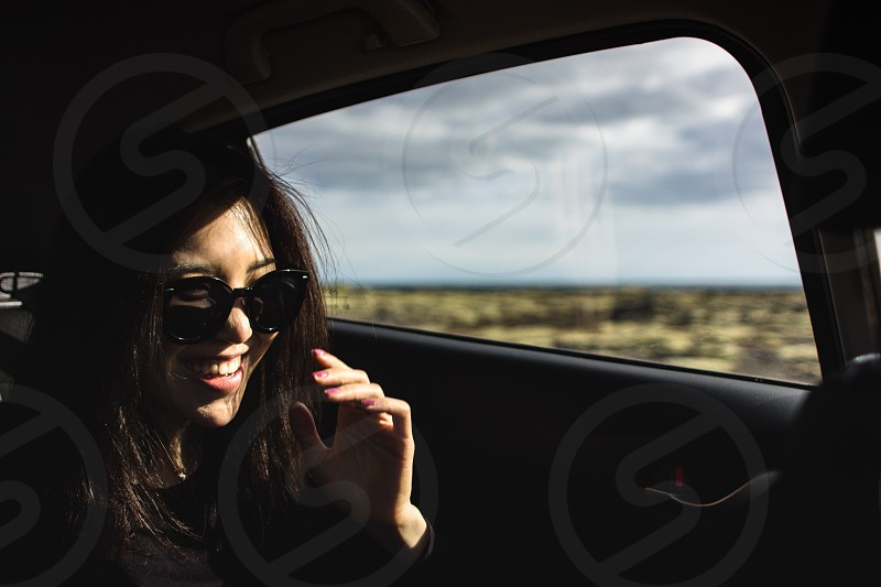 smiling woman wearing black sunglasses near inside car near door with closed window during daytime photo