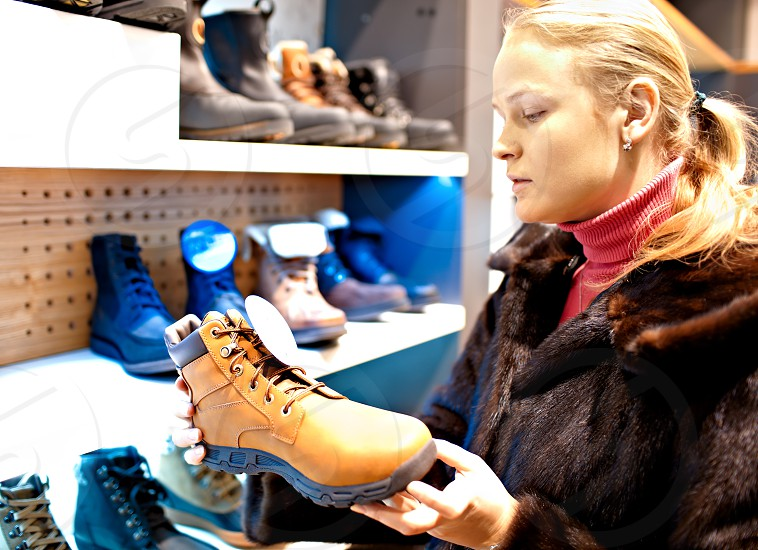 Young caucasian woman is choosing men's winter boots for her husband in a shoe store. photo