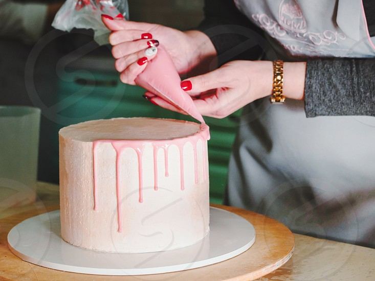Unrecognisable woman decorating mousse glaze cake hands detail focus on the cake. DIY sequence step by step part of series. photo