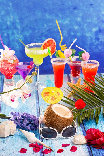 colorful mixed cocktails in tropical blue wood flowers starfish coconut and sunglasses photo