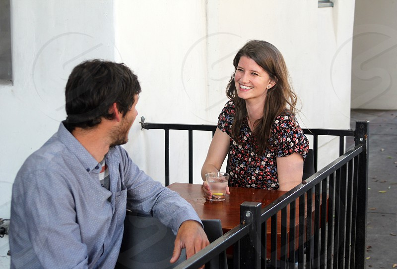Man talking to a woman who is having a drink in an outdoor setting.   photo