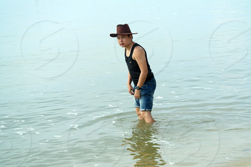 man wearing brown cowboy hat black tank top and blue denim pants standing on body of water during daytime photo