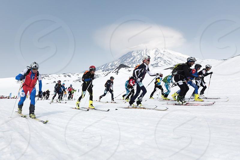 AVACHA KORYAK VOLCANOES KAMCHATKA RUSSIA - APRIL 27 2014: Mass start race ski mountaineers climb on skis on mountain. Team Race ski mountaineering Asian ISMF Russian Kamchatka Championship. photo